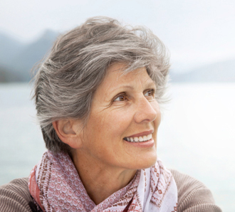 smiling grey haired woman in pink scarf 598 x 298